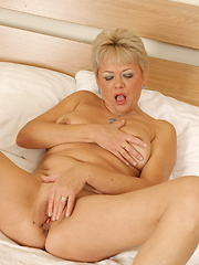 Blonde granny lies on the bed and masturbates by toy